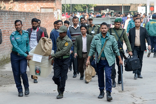 Bangladeshi security personnel carry polling materials at distributing center in Dhaka on December 29, 2018. - Bangladesh stepped up security on December 29 in a bid to contain violence during a general election expected to see Prime Minister Sheikh Hasina win a record fourth term. PHOTO: AFP