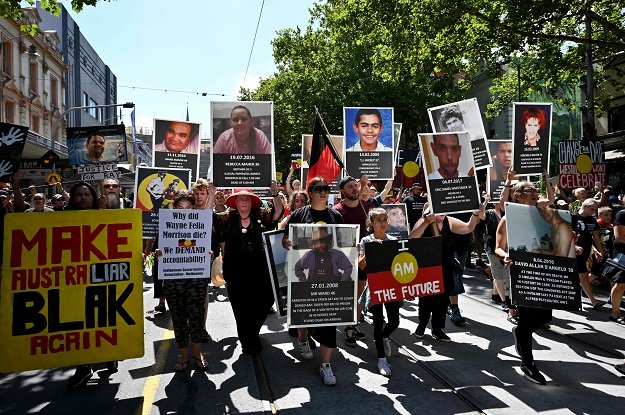 "People hold up placards of Aboriginal people who have allegedly died in police custody, as they take part in an ""Invasion Day"" rally on Australia Day in Melbourne on January 26, 2019. PHOTO: AFP"