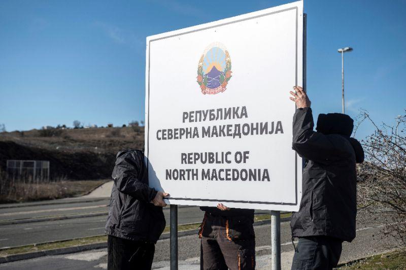 Workers set up a sign reading 'Republic of North Macedonia' at the Macedonia-Greece border near Gevgelija. PHOTO: AFP