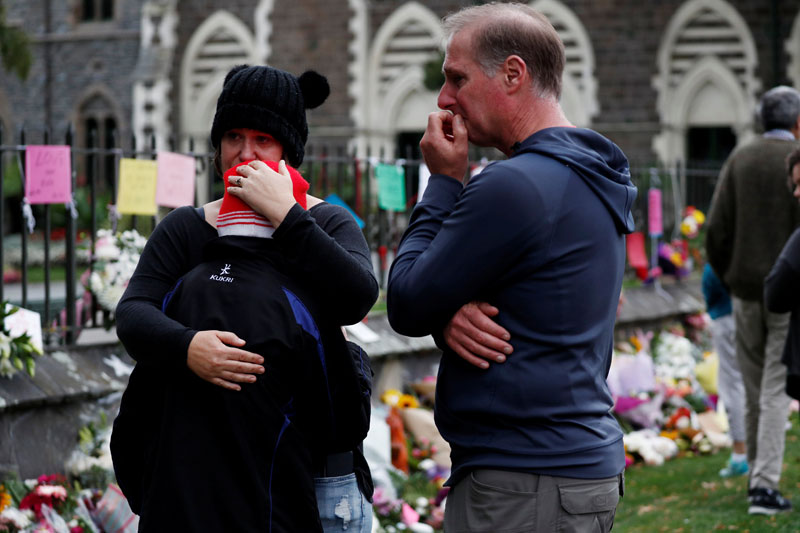 People react at a flower tribute area at Botanical Gardens in Christchurch, New Zealand. PHOTO: REUTERS