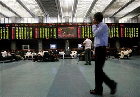 A stockbroker walks near an electronic stock exchange board inside the trading hall at the PSE. PHOTO: REUTERS