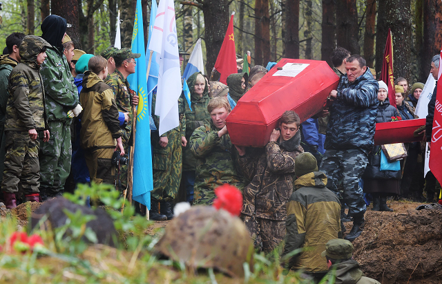Members of volunteer search groups carry coffins with the remains of Red Army soldiers killed in World War Two, into a mass grave during a reburial ceremony at the Sinyavino Heights memorial site outside Saint Petersburg. PHOTO: AFP