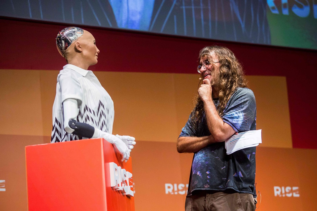 "Chief scientist of Hanson Robotics, Ben Goertzel (R), interacts with ""Sophia the Robot"" (L) during a discussion about the future of humanity in a demonstration of artificial intelligence (AI) by Hanson Robotics. PHOTO: AFP"