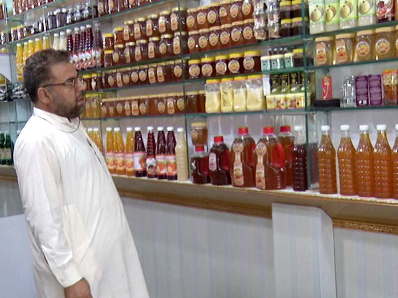 A customer looks at a large variety of honey bottles at a shop that also sells whole beehives in Peshawar . PHOTOS: EXPRESS