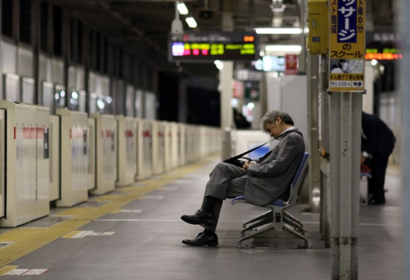 A businessman is seen napping on a bench at a Tokyo train station. PHOTO AFP