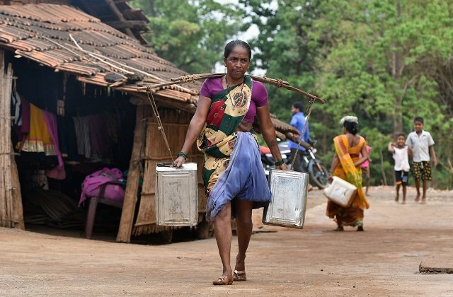 An Indian woman carries water in stainless steel cans at Shakar Pada village near Shahapur, on the outskirts of Mumba. PHOTO: AFP