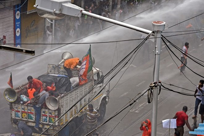 BJP activists shelter on the back of a truck as police use a water canon to disperse demonstrators. PHOTO: AFP