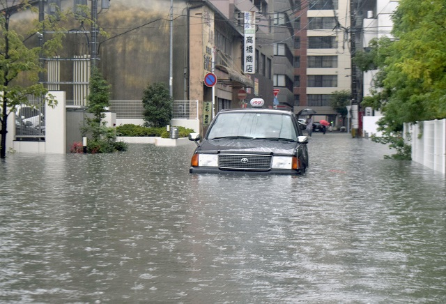 A taxi is stuck in floodwaters caused by heavy rain, in Saga, southern Japan. PHOTO: Reuters