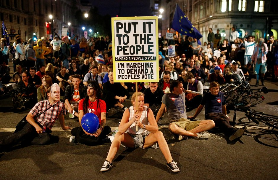 A demonstrator holds a banner, during an anti-Brexit protest, outside the Houses of Parliament in London. PHOTO: Reuters