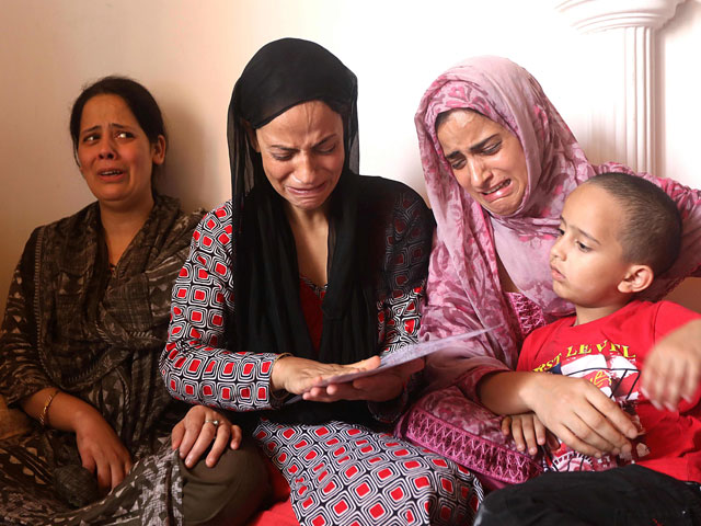 In this photo taken on September 7, 2019, Shaheena (2nd L), the mother of 17-year-old Asrar Khan, cries with relatives as they look at picture of the youth, who she says died on September 3 a month after being fired upon and seriously injured by Indian paramilitary soldiers, in Srinagar. PHOTO: AFP