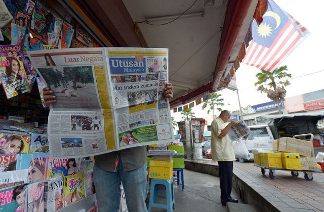 A Malaysian man reads a newspaper outside a shop in downtown Kuala Lumpur on October 10, 2012.  PHOTO: AFP