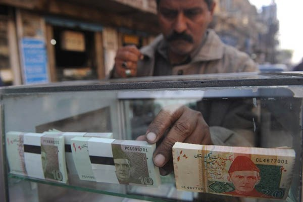 A vendor arranges 10 and 20-rupee Pakistani bank notes in a display shelf at a commercial area in Karachi. PHOTO: AFP