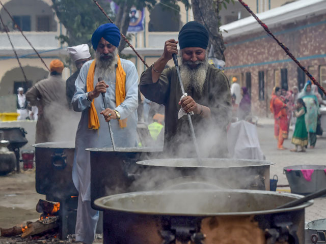 In this picture taken on November 6, 2019 Sikh pilgrims walk in front of the Shrine of Baba Guru Nanak Dev at the Gurdwara Darbar Sahib ahead of its opening, in the Pakistani town of Kartarpur near the Indian border. - Thousands of Sikh pilgrims are expected around the world to visit to Pakistan to celebrate the 550th birth anniversary of Sri Guru Nanak Dev which falls on November 12. PHOTO: AFP