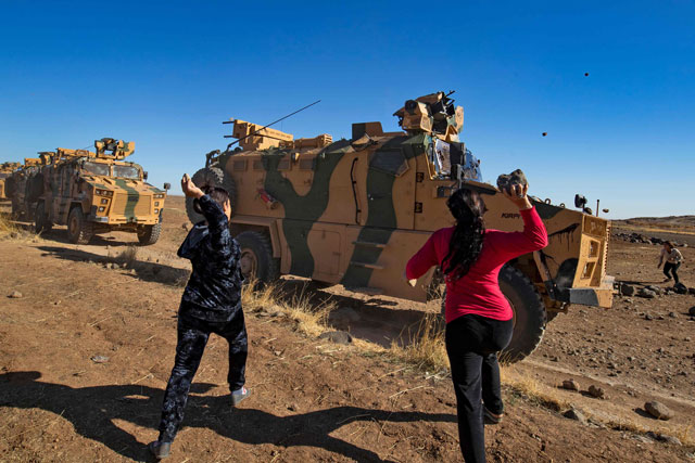 Kurdish demonstrators hurl rocks at a Turkish military vehicle on November 8, 2019, during a joint Turkish-Russian patrol near the town of Al-Muabbadah in the northeastern part of Hassakah on the Syrian border with Turkey. PHOTO: AFP