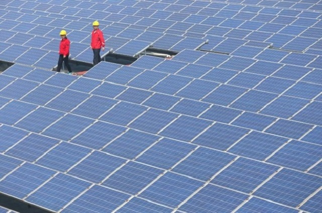 Workers walk past solar panels in Jimo, Shandong Province, China, April 21, 2016. PHOTO: REUTERS