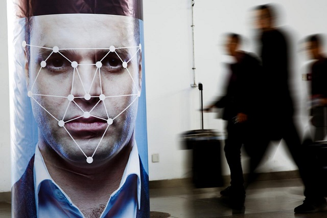 FILE PHOTO:People walk past a poster simulating facial recognition software at the Security China 2018 exhibition on public safety and security in Beijing, China October 24, 2018. PHOTO: REUTERS