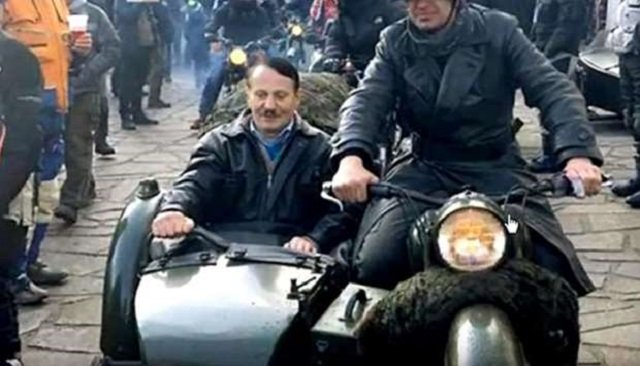 He sported a toothbrush moustache and was seated in the sidecar of a bike driven by a man dressed as a 1940s-era soldier, complete with World War II-style helmet. SCREEN GRAB