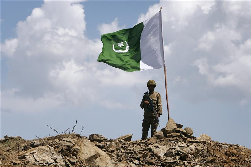 A Pakistani soldier poses for a photo under Pakistan's national flag planted atop the Baine Baba Ziarat mountain in Swat district. PHOTO: REUTERS