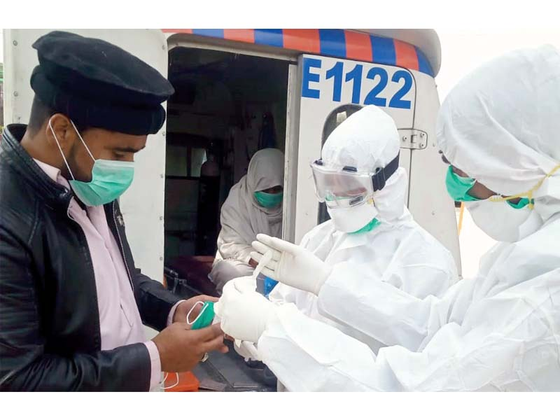 Health workers in safety gear prepare to shift a suspected coronavirus patient to Pims. PHOTO: EXPRESS