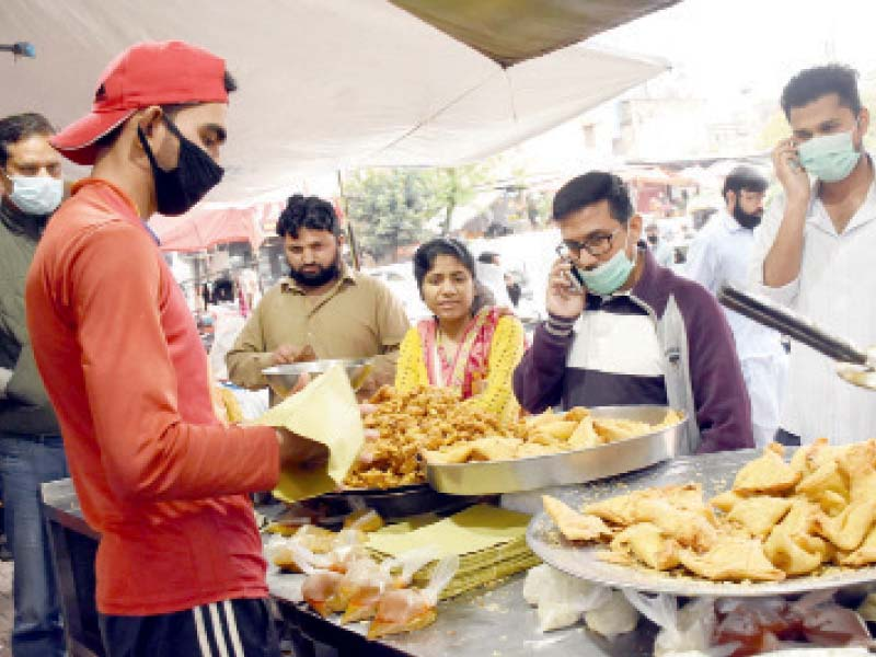 People ignore social distancing and self-isolation but wear masks as they buy fried items from a shop in the Karachi Company area of Islamabad on Tuesday. PHOTO: ONLINE