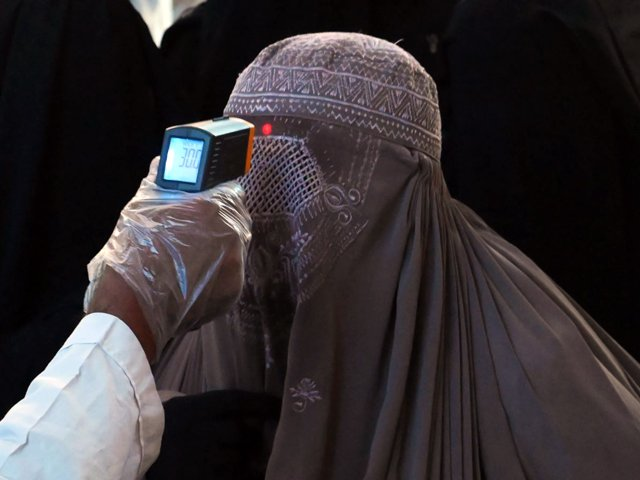 A health worker checks the body temperature of a burqa-clad woman passenger amid concerns over the spread of the novel coronavirus at the railway station in Lahore. PHOTO: AFP/FILE