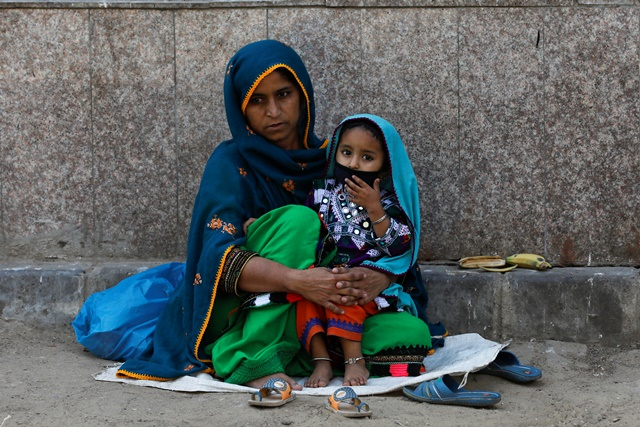 Three-year-old Nadia wears protective mask sitting on her mother's lap, as they are waiting to visit an ailing family member, outside a hospital during a lockdown after Pakistan shut all markets, public places and discouraged large gatherings amid an outbreak of coronavirus disease (COVID-19), in Karachi, Pakistan, April 1, 2020. REUTERS/Akhtar Soomro