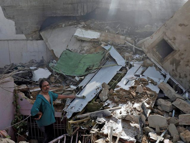 A man stands on the debris of a house at the site of a passenger plane crash in a residential area near airport in Karachi. PHOTO: REUTERS