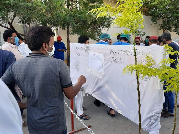 A man looks at a list of the deceased and injured brought in to JPMC from the crash site, posted at an information desk outside the hospital. Many of the bodies remain unidentified. PHOTO: EXPRESS