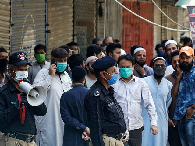 A police officer uses a megaphone to disperse shopkeepers gathered to reopen their shops at a closed market in Karachi. PHOTO: REUTERS/FILE