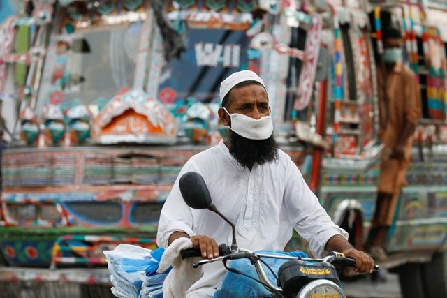 A man wearing a protective face mask rides a motorbike, as the outbreak of the coronavirus disease (COVID-19) continues, in Karachi, Pakistan June 11, 2020. REUTERS