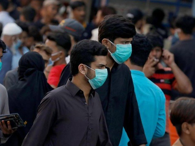 Men wearing protective face masks walk amid the rush of people outside a market as the outbreak of the coronavirus disease (Covid-19) continues, in Karachi. PHOTO: REUTERS/FILE