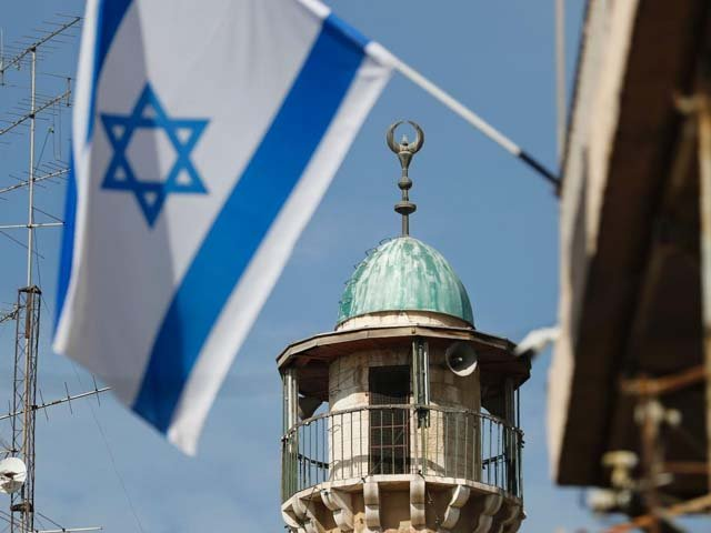 An Israeli flag waves in front of the minaret of a mosque in the Arab quarter of Jerusalem's Old City, November 14. Israeli Prime Minister Benjamin Netanyahu said he backed a bill limiting the volume of calls to prayer from mosques, a proposal government watchdogs called a threat to religious freedom.