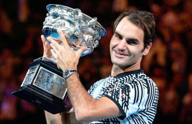 Switzerland's Roger Federer celebrates with the championship trophy during the awards ceremony after his victory against Spain's Rafael Nadal in the men's singles final of the Australian Open in Melbourne on January 29, 2017 PHOTO: AFP/WILLIAM WEST