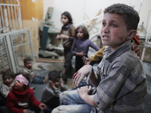 Syrian children wait to receive treatment at a makeshift clinic following reported air strikes by government forces in the rebel-held town of Douma, on the eastern outskirts of Damascus. PHOTO: AFP