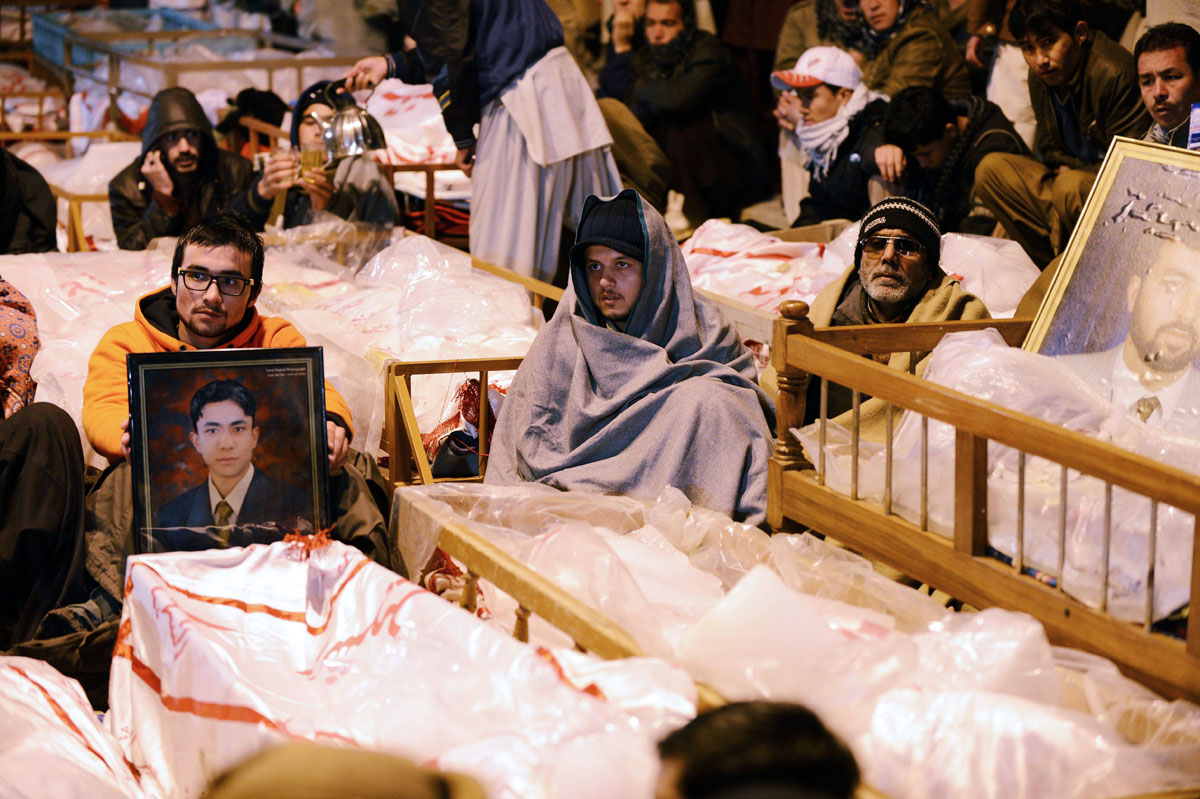 Shia  Muslims demonstrate and sit amongst the coffins and portraits of bomb blast victims in Quetta on January 12, 2013. PHOTO: AFP