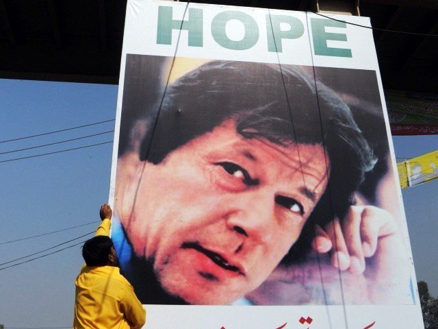 A worker installs a banner showing a portrait of Pakistani politician Imran Khan on a busy street in Lahore on October 27, 2011. PHOTO: AFP