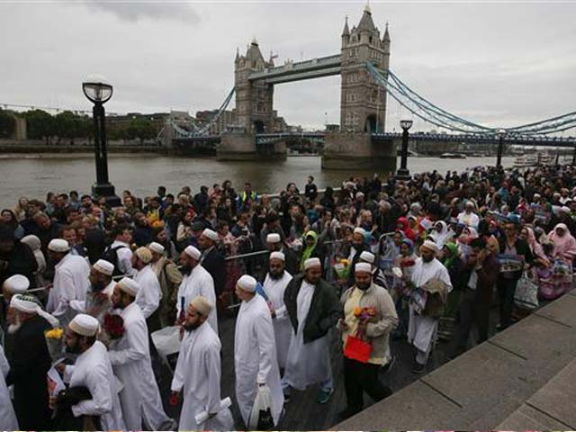Members of the Dawoodi Bohra Muslim community (in white) join others as they bow their heads during a vigil at Potters Fields Park in London on June 5, 2017 to commemorate the victims of the terror attack on London Bridge and at Borough Market that killed seven people on June 3. PHOTO: AFP