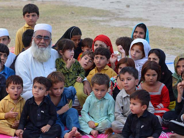 Gulzar Khan, who fled with his family following a military operation against militants in the North Waziristan tribal agency, pictured with some of his children in Bannu. PHOTO: AFP