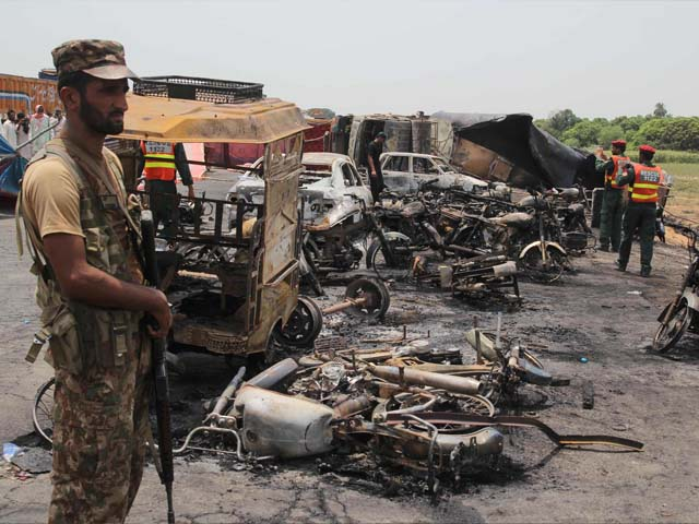 Pakistani soldiers stand guard beside burnt out vehicles at the scene where an oil tanker caught fire following an accident on a highway near the town of Ahmedpur East, some 670 kms (416 miles) from Islamabad on June 25, 2017. At least 123 people were killed and scores injured in an inferno that erupted after an oil tanker overturned in central Pakistan early on June 25 and crowds rushed to collect fuel, an official said. PHOTO: AFP  / SS MIRZA