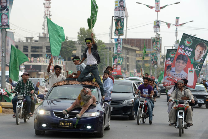 Activists of Pakistan Tehreek-e-Insaf (PTI) and Pakistan Muslim League Nawaz (PML-N) parties carry posters and flags as they drive during the general election in Rawalpindi. PHOTO: GETTY