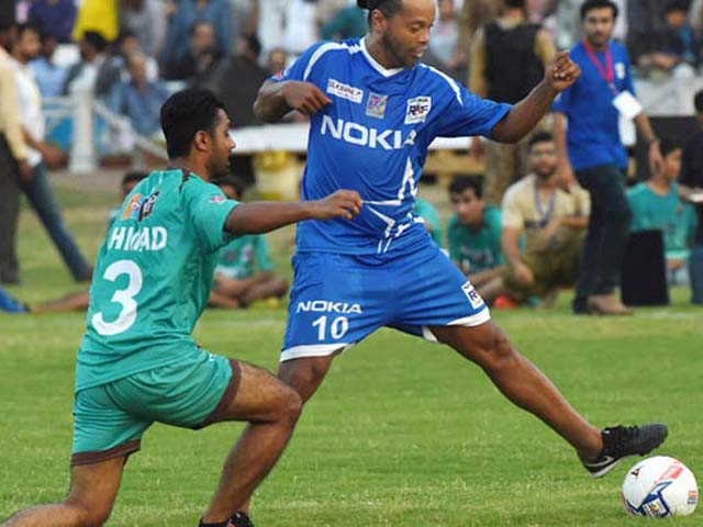 Former player for FC Barcelona Brazilian Ronaldinho (R) vies with Pakistani football players during a friendly match on July 9, 2017 in Lahore.  Eight of football's biggest stars, including Brazilian hero Ronaldinho, will play two exhibition matches in Pakistan this weekend in hopes of attracting more players from the cricket-mad country. PHOTO: AFP / ARIF ALI