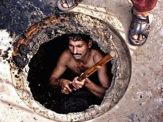 Sanitary worker taking garbage out of the gutter with no safety equipment. PHOTO: WORLDWATCHMONITOR