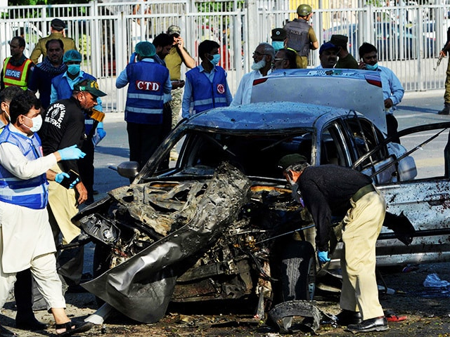 Security officials inspect a destroyed vehicle after an explosion in Lahore. PHOTO: AFP