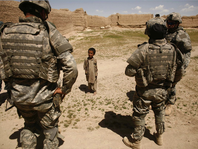 An Afghan boy looks at US soldiers as they patrol a village near the town of Makkor, southwest of Kabul, April 20, 2007. PHOTO: REUTERS