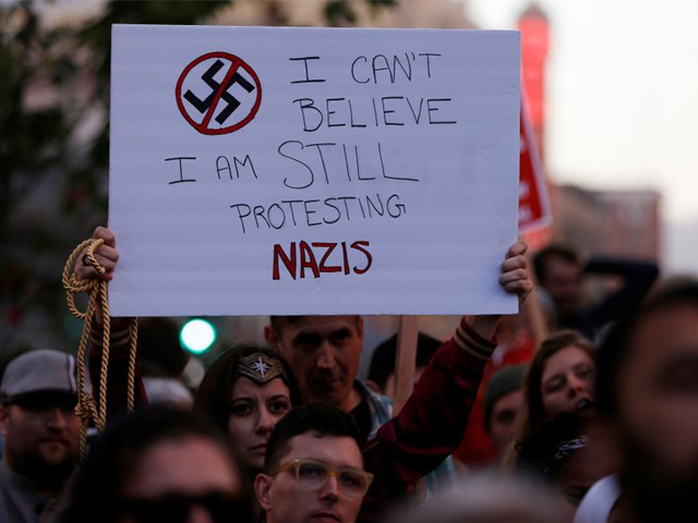 """A demonstrator holds signs during a rally in response to the Charlottesville, Virginia car attack on counter-protesters after the """"Unite the Right"""" rally organized by white nationalists, in Oakland, California, U.S., August 12, 2017. PHOTO: REUTERS"""
