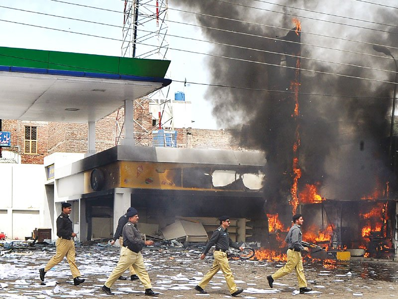 A file photo of a policemen walking across a petrol station gutted in a violent protest related to power issues. PHOTO: AFP