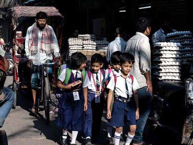 File photo of Indian pupils walking to school along a busy street. PHOTO: AFP