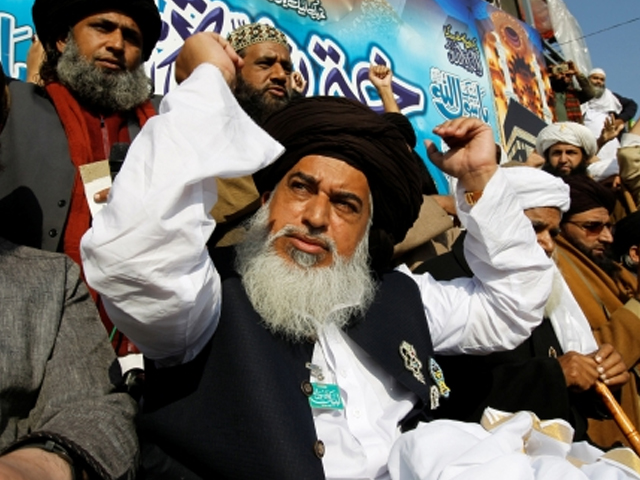 Khadim Hussain Rizvi (C), leader of Tehrik-e-Labaik Pakistan political party, raises his arms as supporters chant slogans at their protest site at Faizabad junction in Islamabad, Pakistan on November 27, 2017. PHOTO: REUTERS