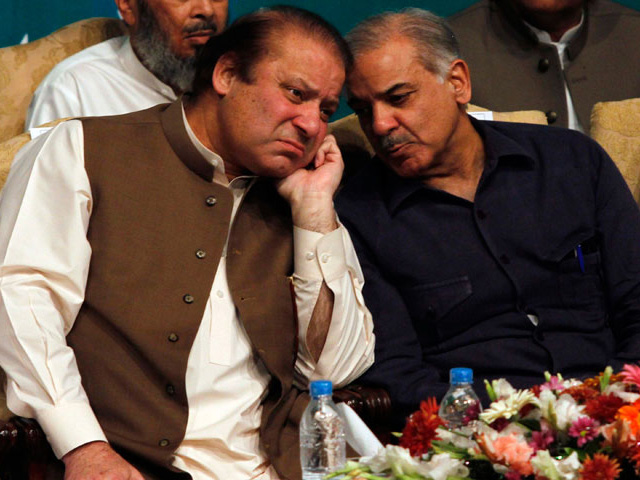Nawaz Sharif (L), incoming prime minister and leader of PML-N, talks with his brother Shahbaz Sharif before addressing his party members who were voted to political posts in the general election, during a function in Lahore, May 30, 2013. PHOTO: REUTERS