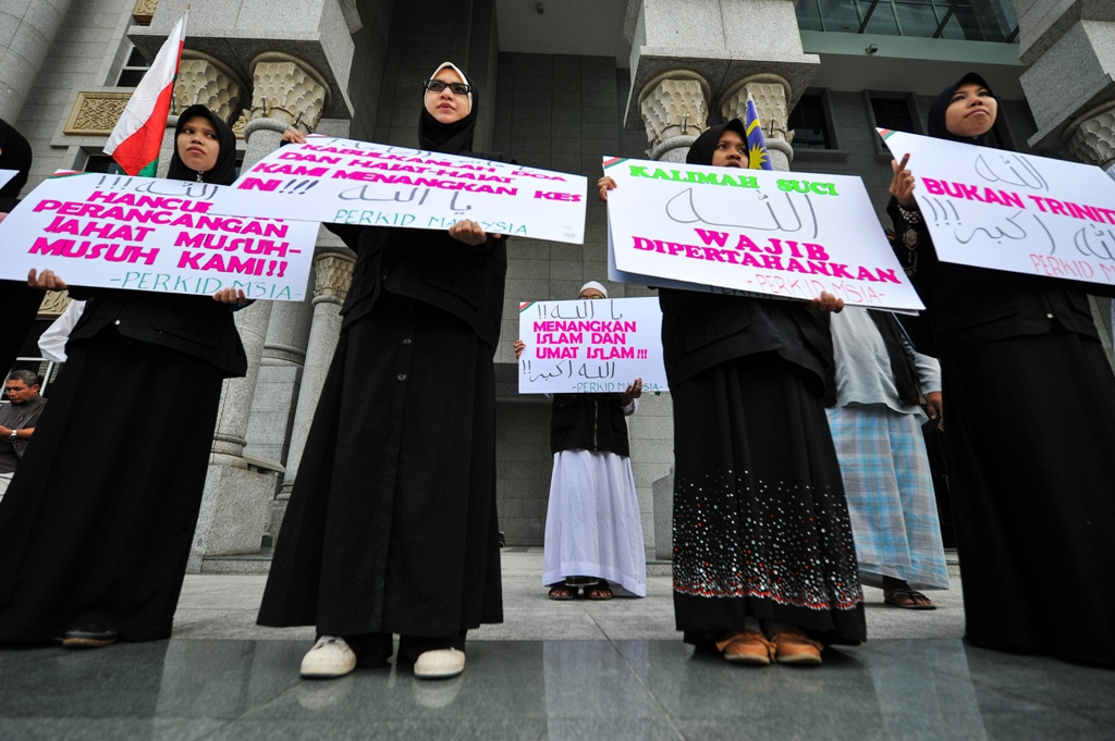 Protesters display placards during a demonstration at the court of appeal in Putrajaya. PHOTO: AFP
